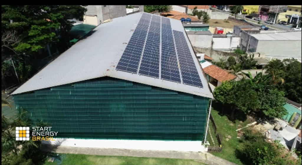 Placas de energia solar instaladas no telhado da quadra principal do colégio Prígule