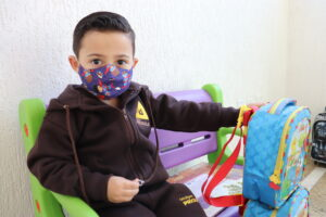 criança, sentada no banco do colégio, utilizando máscara e segurando sua mochila
